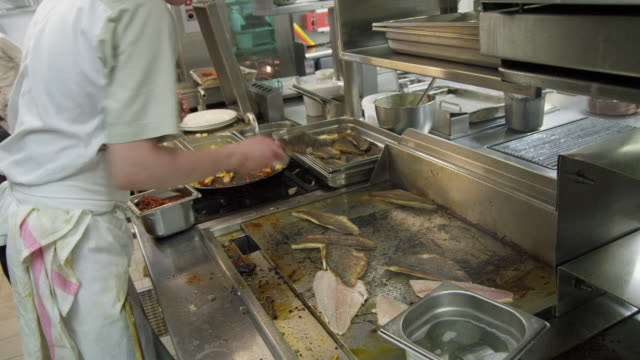 POV cook working on hot plate cooking fish in a restaurant kitchen