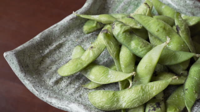 cooked green organic edamame with salt turning, japanese food - plant pod stock videos & royalty-free footage
