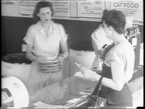 A cooked prepackaged TV dinner / woman enters a frozen food center and purchases frozen meals for her family / a woman pulls frozen dinners from...