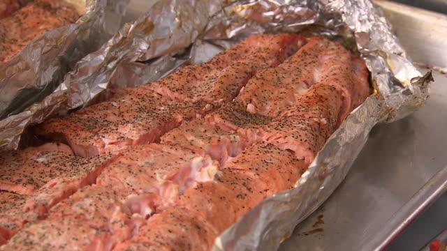 """CU of cooked salmon in tin foil, pans down, Metlakatla, Annette Island, Alexander Archipelago, Alaska."""