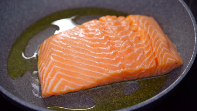 cooking a fresh salmon steak in olive oil - salmon steak stock videos & royalty-free footage