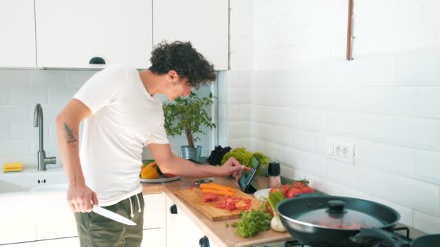 vídeos de stock, filmes e b-roll de cozinhar uma receita nova. - homens jovens