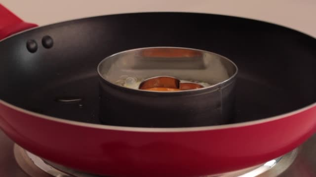 cooking an egg fried with a heart yolk in a pan - egg yolk stock videos & royalty-free footage