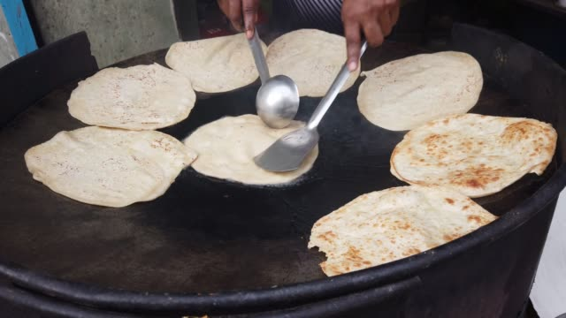 cooking and preparation of roti or indian flatbread of flour and cooking on a large open pan at a dhaba or a highway restaurant - sweet food stock videos & royalty-free footage