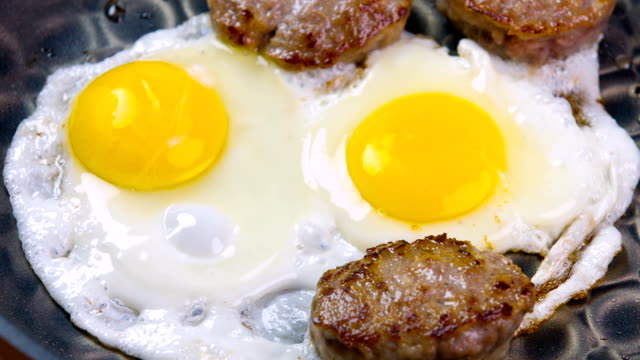 cooking breakfast fresh egg and sausage - sausage stock videos & royalty-free footage