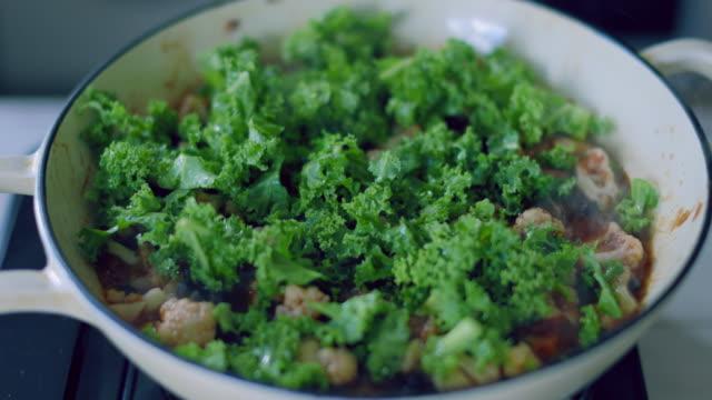 カリフラワーの黒豆とケールシチューを調理する - 煮込み料理点の映像素材/bロール