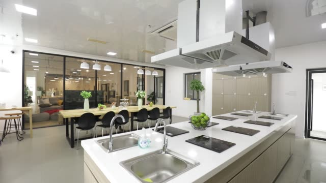 cooking facilities and a communal dining table stand in the kitchen at china vanke co's port apartment project in shanghai china on friday dec 29... - gourmet küche stock-videos und b-roll-filmmaterial