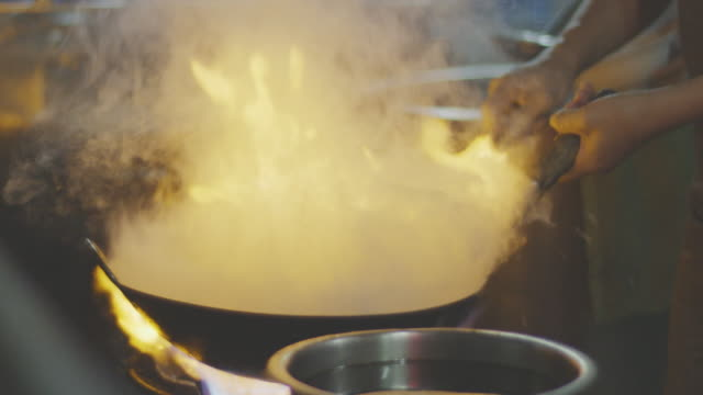 vídeos de stock e filmes b-roll de cooking food in flaming skillet,close up 4k slo mo - comida chinesa
