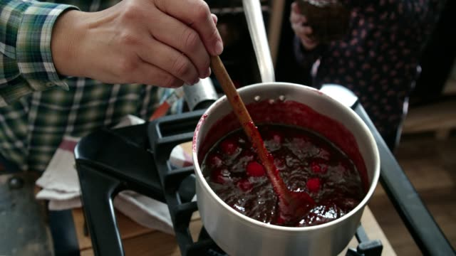 cooking homemade raspberry jam in domestic kitchen - preserve stock videos and b-roll footage