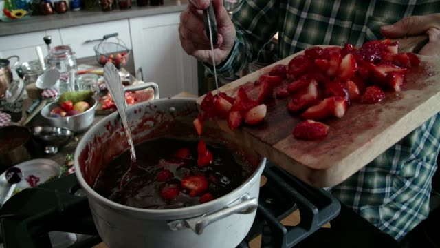 cooking homemade strawberry jam in domestic kitchen - canning stock videos & royalty-free footage