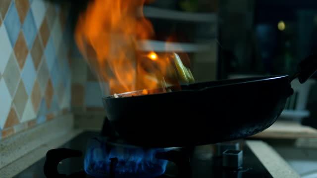 vídeos de stock, filmes e b-roll de cozinhando em panela flamejante - panning