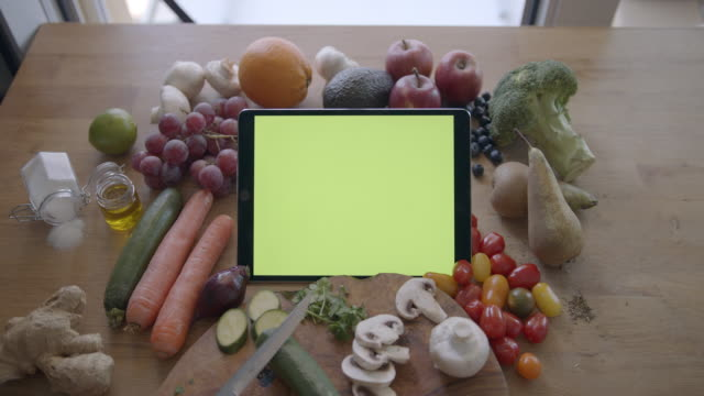 cooking in kitchen while looking at digital tablet with green screen, surrounded by fresh food and vegetables - digital tablet stock videos & royalty-free footage