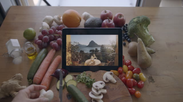 cooking in kitchen while looking at digital tablet with images of food, surrounded by fresh food and vegetables - grape stock videos & royalty-free footage