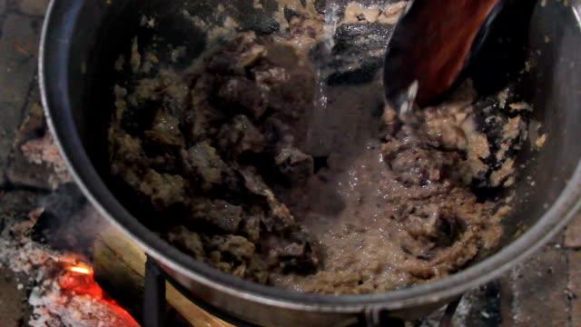 Cooking in metal pan on bonfire