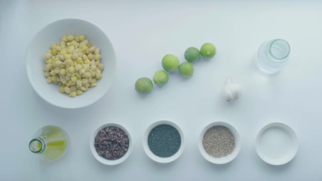 cooking ingredients on a white table: chickpeas, lemons, garlic, water bottle, olive oil bottle, black quinoa, black sesame, cumin and salt - black olive stock videos & royalty-free footage