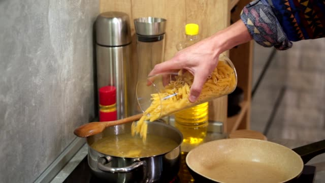 cooking man boiling pasta in a saucepan at home - boiling stock videos & royalty-free footage