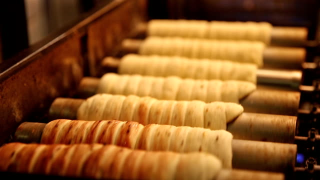 Cooking of trdelnik traditional national Czech sweet pastry dough.