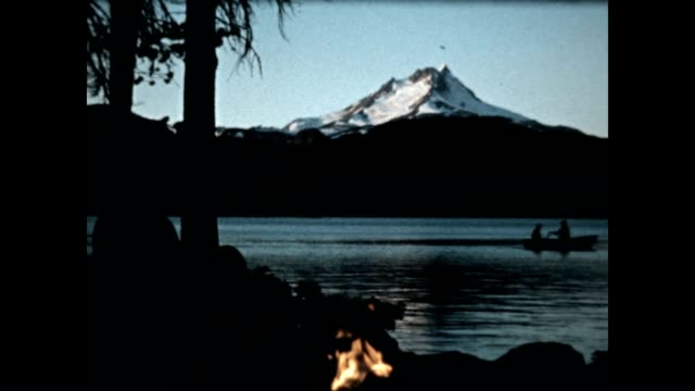 cooking on a campfire at bench lake / a man rows a boat with a scenic view of mount rainier in the background. - mt rainier stock videos & royalty-free footage