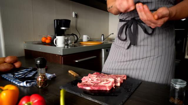vídeos y material grabado en eventos de stock de cocinar carne de cerdo en la cocina - frescura