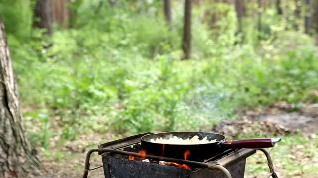 stockvideo's en b-roll-footage met koken van aardappelen op het kampvuur. - braadpan