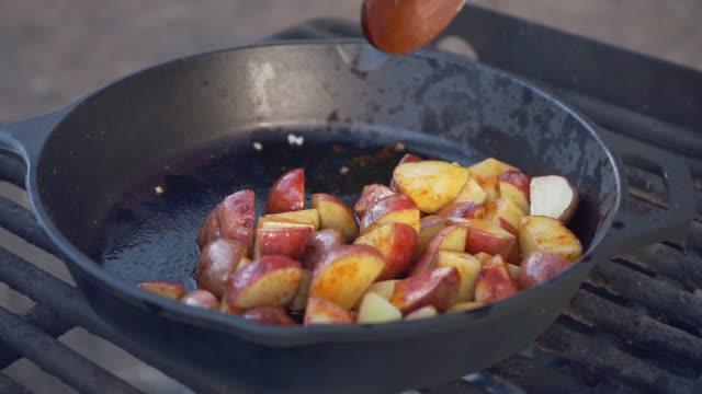 vidéos et rushes de cooking potatoes over a campfire - table de pique nique