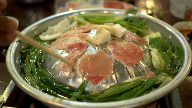 cooking raw pork and fresh vegetable on hot pan as called Moo Kra Ta