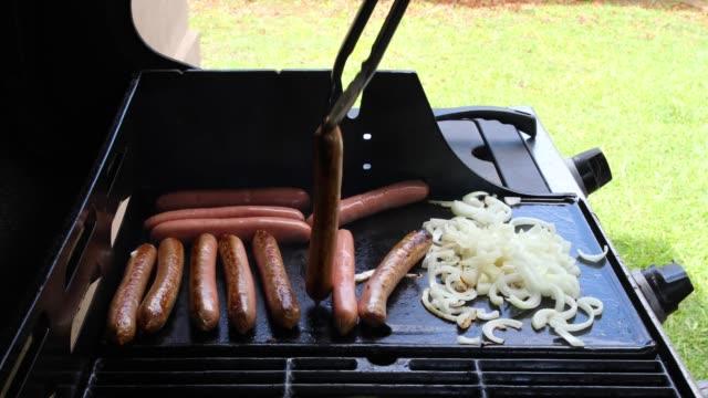 kochen, würstchen und zwiebeln auf outdoor-grill - fleischzange stock-videos und b-roll-filmmaterial