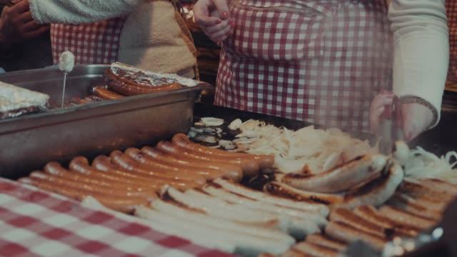 vídeos de stock, filmes e b-roll de cozinhar salsichas sobre o churrasco - festival tradicional