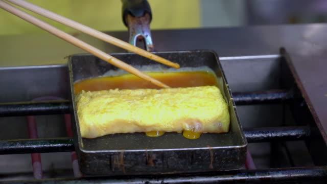 vídeos y material grabado en eventos de stock de cocinar tamagoyaki en la estufa, tortilla de huevo japonés. - sofrito