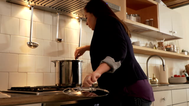Cooking time. Women enters the kitchen and checks on soup