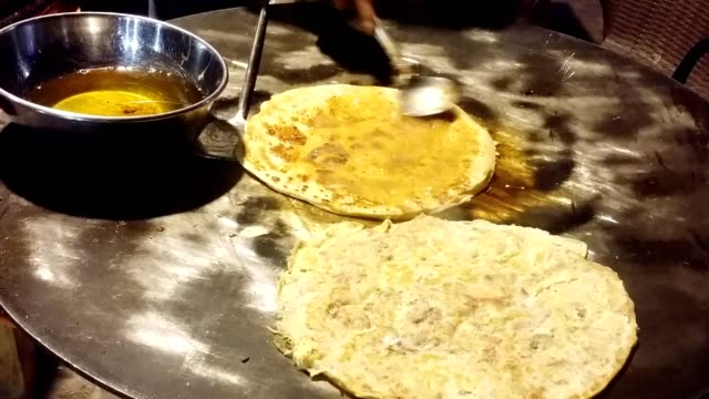 cooking traditional asian (pakistani) paratha (oily flatbread) with egg on top - punjab pakistan stock videos and b-roll footage