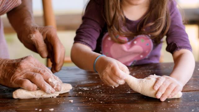 vídeos de stock, filmes e b-roll de cozinhar com a vovó-linda menina aprenda como fazer cookies na clara luz natural vintage cozinha - massa alimento básico