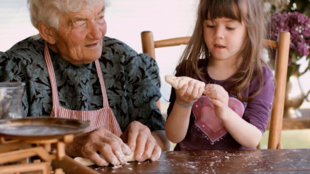 Kochen mit Oma-schöne Mädchen lernen, wie Sie Cookies in den hell beleuchteten Vintage-Küche