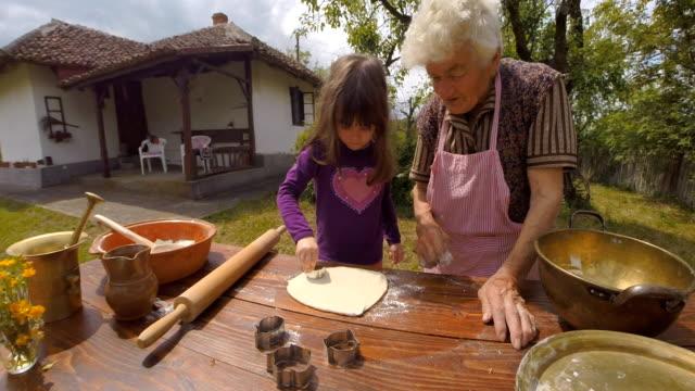 Matlagning med mormor-vackra lilla flickan lär sig att göra kakor i Bright-lit Vintage kök