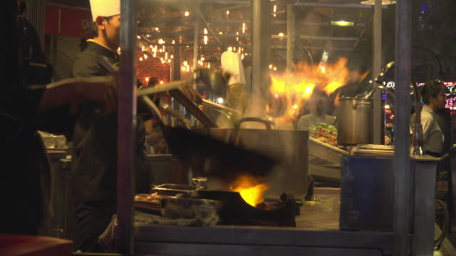 cooking with wok on fire in open kitchen in pub street - cooker stock videos & royalty-free footage