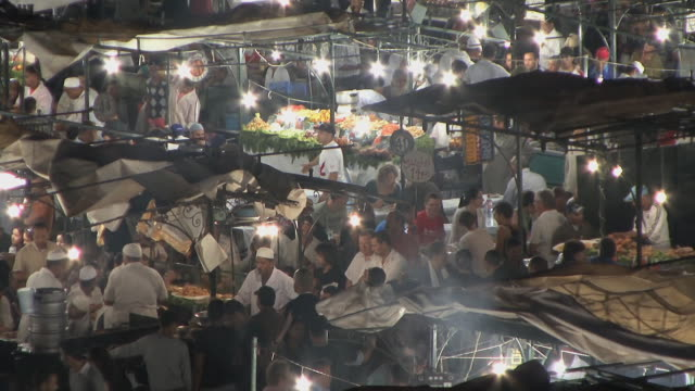ws ha td cooks and customers at crowded market in djemaa el fna square, marrakech, morocco - モロッコ文化点の映像素材/bロール