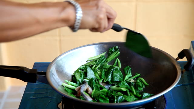cooks and stir-fried kale. - kale stock videos and b-roll footage