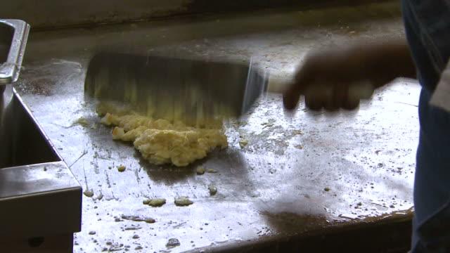vídeos de stock, filmes e b-roll de cu cook's hand scrambling eggs in diner kitchen / washington district of columbia united states - espátula