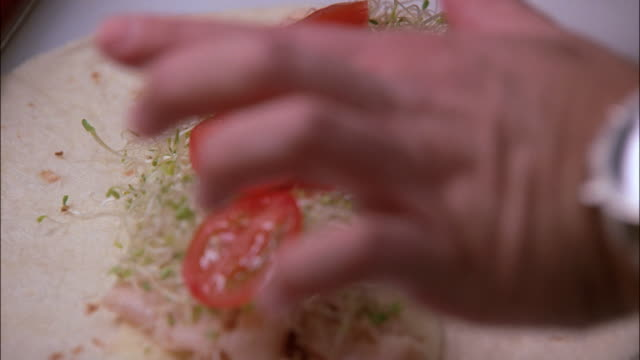 CU Cook's hands rolling a sandwich wrap / New York, United States