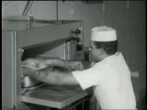 cooks prepare turkeys vegetables and rolls in a restaurant kitchen - anno 1960 video stock e b–roll