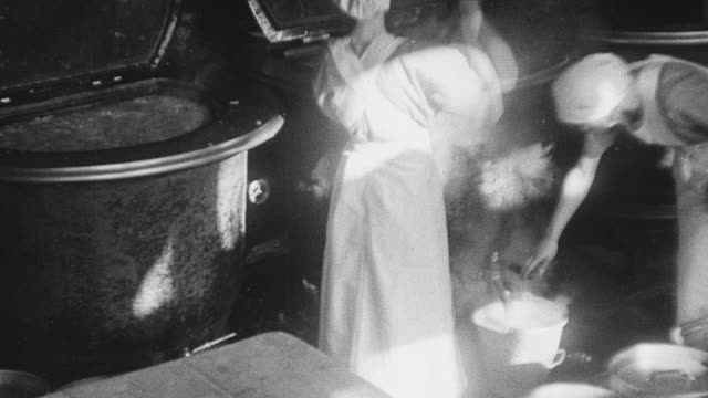 1925 MONTAGE Cooks stirring vat of steaming liquid and tapping liquid into pails, packing prepared meals into wooden containers and carrying containers from the kitchen to van waiting outside / Newcastle upon Tyne, England, United Kingdom