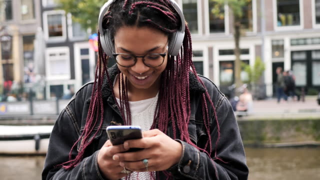 vídeos de stock e filmes b-roll de cool african mixed-race teenager with braided hair in the city - braided hair