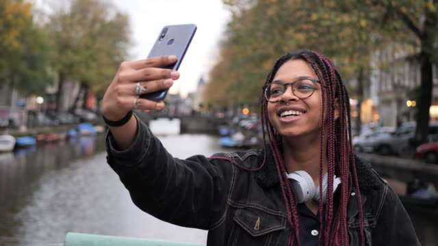 cool african mixed-race teenager with braided hair taking selfie - freedom stock videos & royalty-free footage
