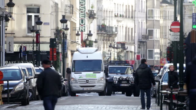 a cool autumn morning in brussels cars pedestrians cyclists on a small street filmed by a telephoto lens no - telephoto lens stock videos and b-roll footage