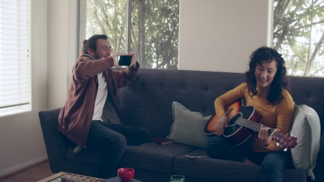 ms cool couple hanging out at home together - strumento musicale video stock e b–roll