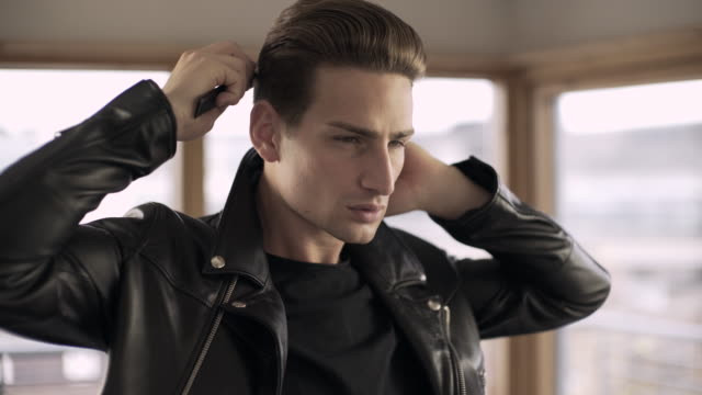 A cool dude in a leather jacket combing his hair.