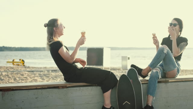 cool female friends having ice cream in the sunset - tattoo stock videos & royalty-free footage