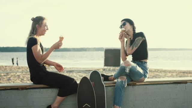 夕日 (スローモーション) にアイスクリームを持つクールな女性の友人