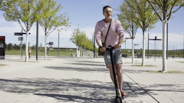 stockvideo's en b-roll-footage met cool, fit and active senior man in his 60s enjoys a sunny ride on his trendy black e-scooter. - casual clothing