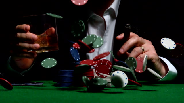 vídeos de stock, filmes e b-roll de cool gambler sentado atrás de batata chips chovendo - cassino